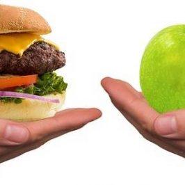 Twee handen met een hamburger en fruit