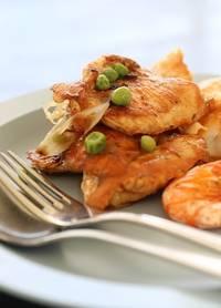 Gebakken kip op een bord met dorperwtjes er bij
