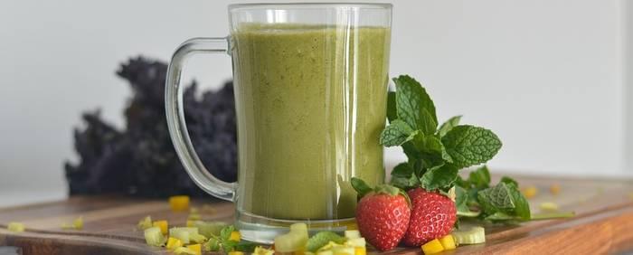 Een gezonde groene smoothie met een aardbei er naast