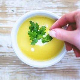 Drie witte soepkommen met gele soep er in