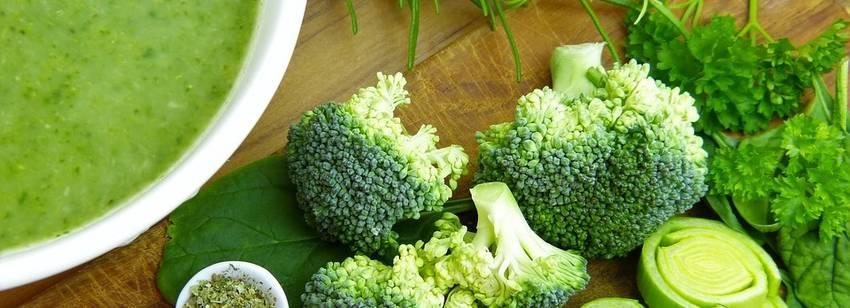 Broccolisoep in een soepkom met er omheen broccoli