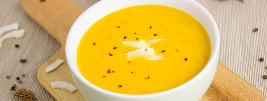 Oranje pompoensoep in een witte soepkom