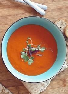 Rode tomatensoep in een blauwe soepkom
